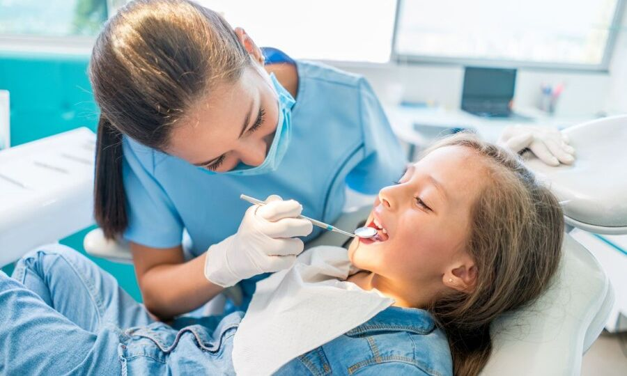 Young girl sitting on dental chair getting her teeth checked by a dentist