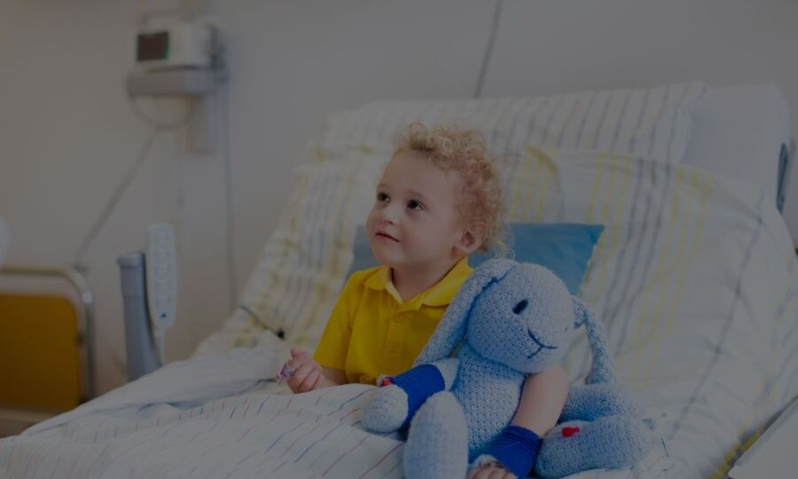 Young boy on hospital holding a stuffed toy before general anesthesia treatment