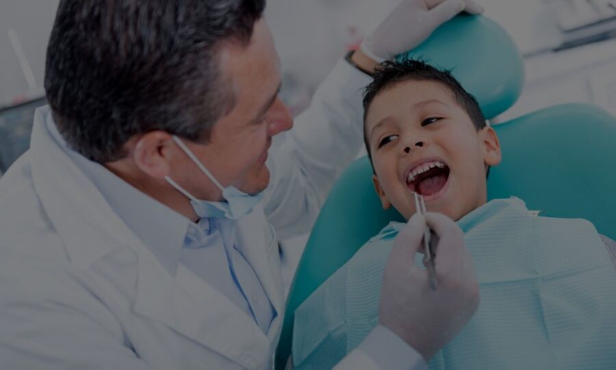 Young boy with mouth open getting teeth checked by pediatric dentist