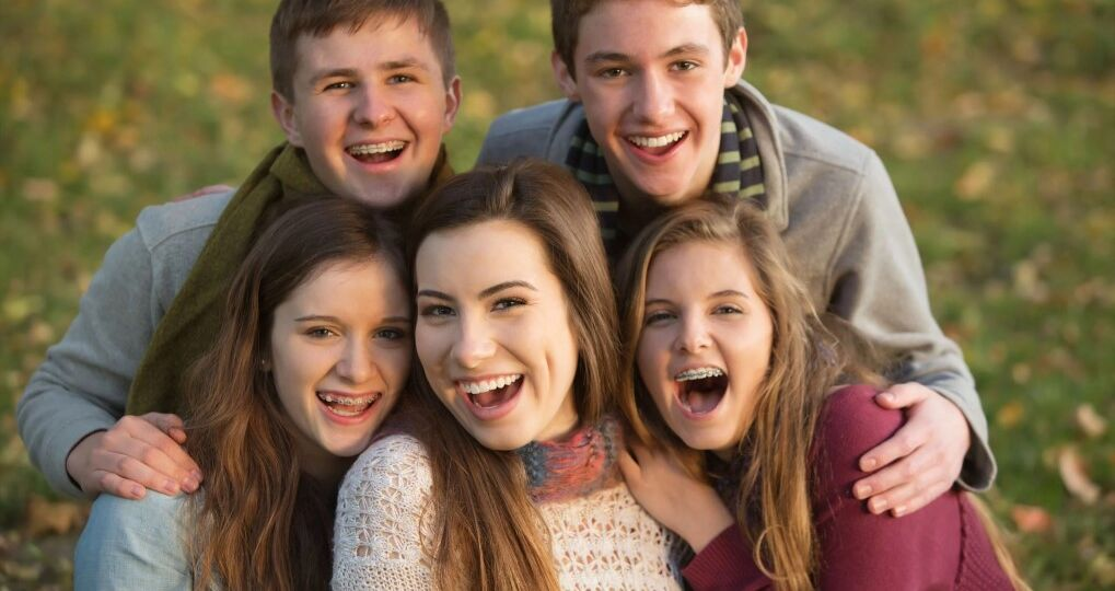 A group of teens with braces smiling