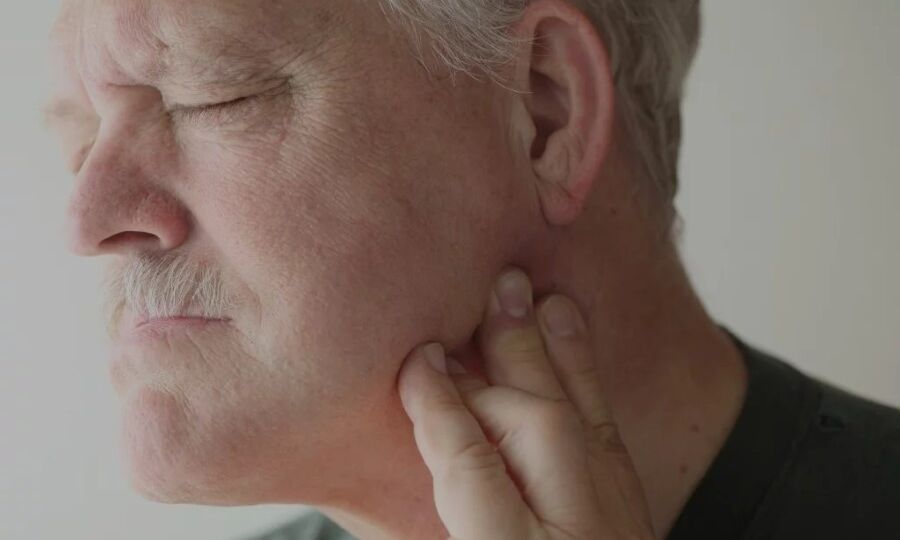 Man experiencing TMD pain holding jaw with left hand
