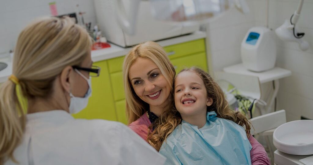 Mother and young daughter smiling while talking to a dentist