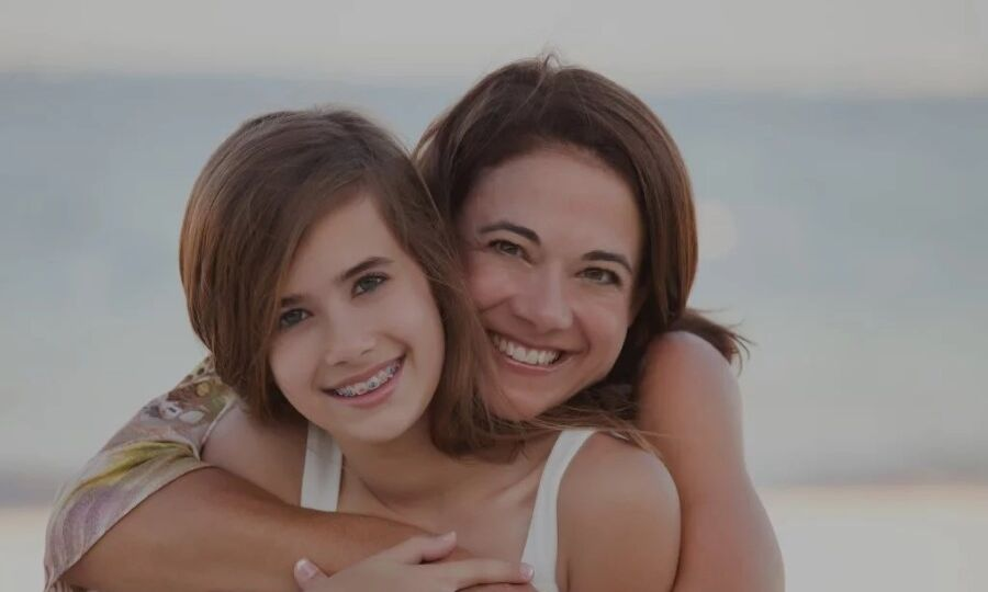 Mother hugging teenage daughter with braces