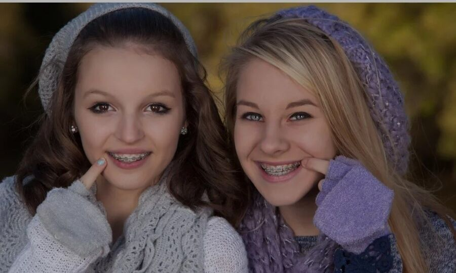 Two teen girls with braces pointing towards their mouths