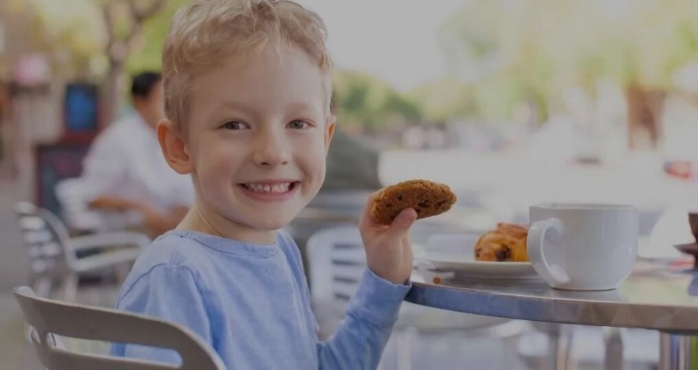 Young boy smiling while holding a cookie