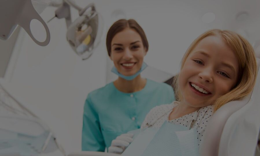 Young girl on a dental chair and a pedaitric dentist smiling