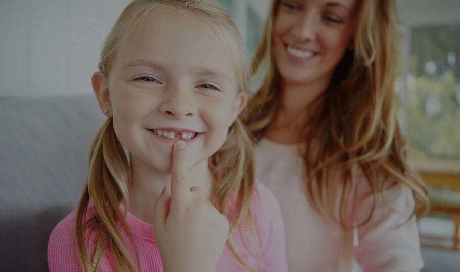 Young girl smiling and ponting her missing tooth
