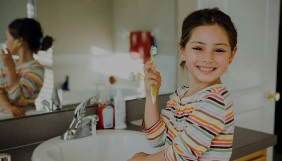 Young girl smiling while holding up a toothbrush practicing home dental care