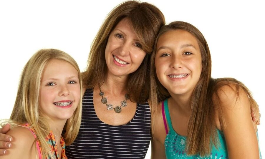 Mother and two teen daughters with braces smiling