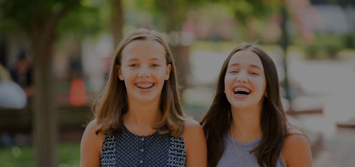 Two teen girls with braces laughing while out in the park