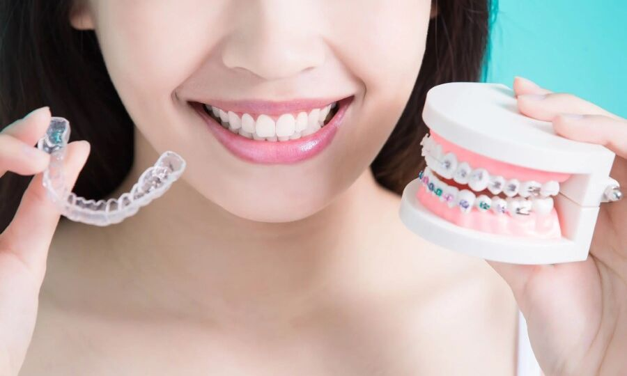 Woman comparing Invisalign clear aligner and braces
