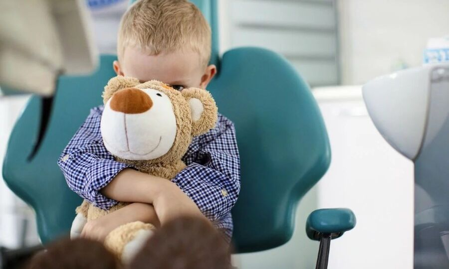 Young boy hiding behind a teddy bear scared of the dentist