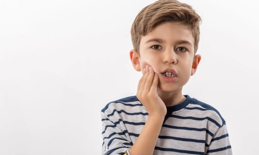 Young boy holding right cheek experiencing pain from tooth cavity