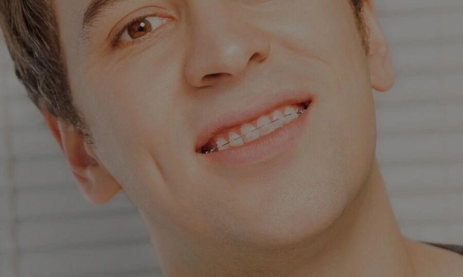 Young man with clear braces smiling