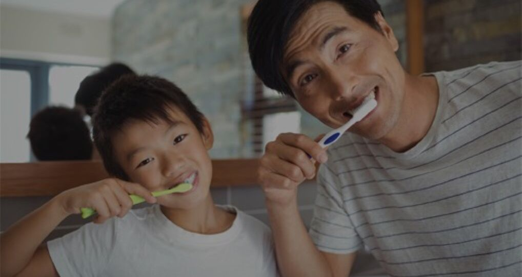 Father and son brushing teeth together with fluoride toothpaste