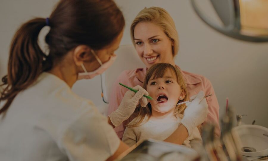 Mother holding young daughter while getting her first dental filling