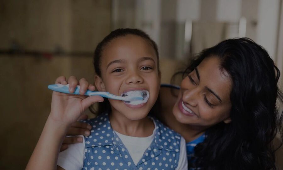 Mother looking at young daughter while brushing her teeth