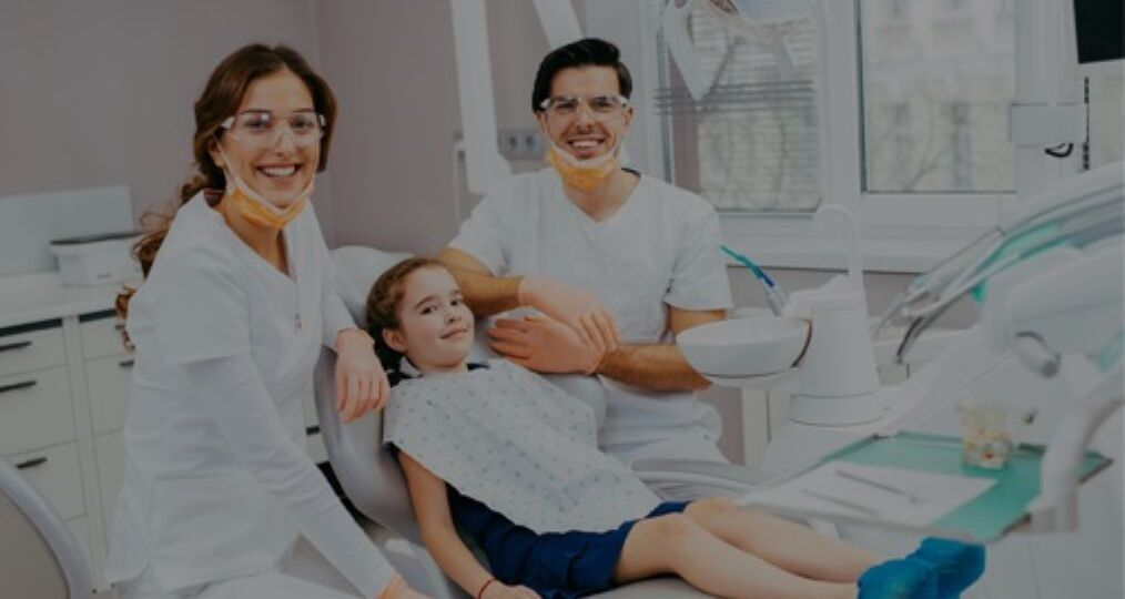 Young girl lying on dental chair with dentist and dental assistant