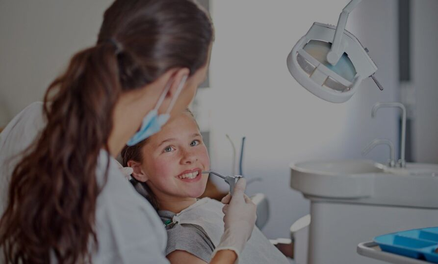Young girl smiling at dental assistant while getting dental treatment