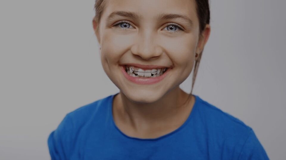 Young girl wearing a blue shirt with braces smiling