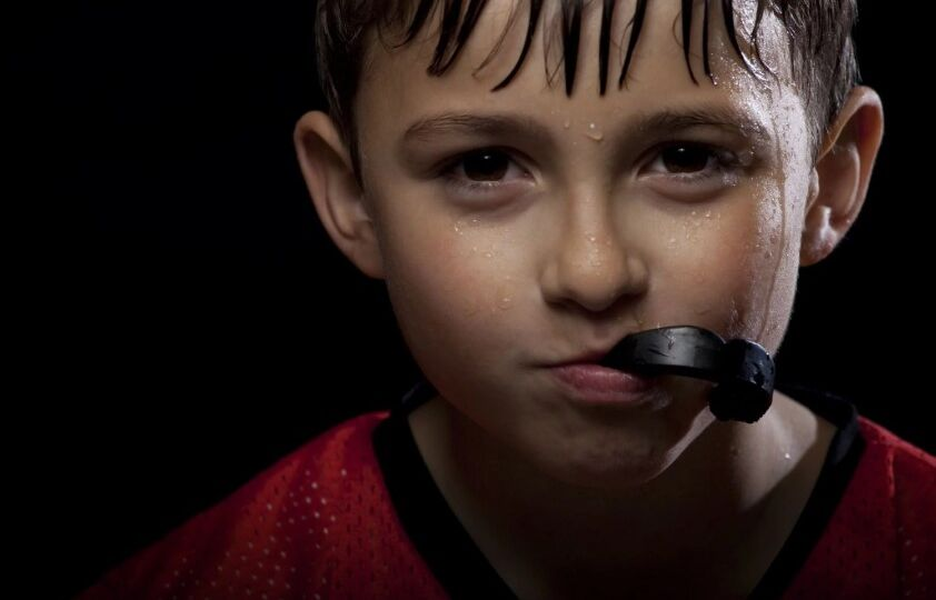 Young athletic boy holds sports mouthguard wiith mouth