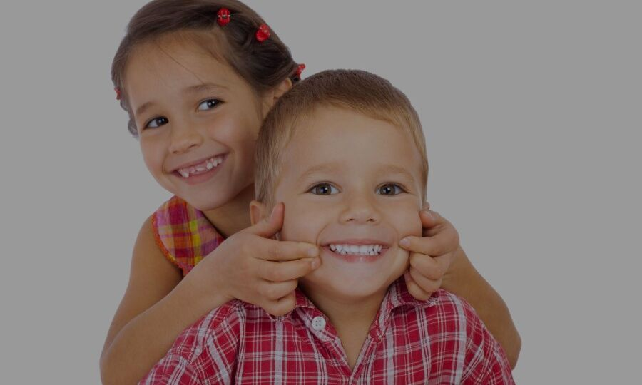 Young girl holds younger sibling's mouth to show teeth